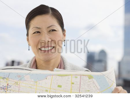 Middle-aged Asian woman holding map