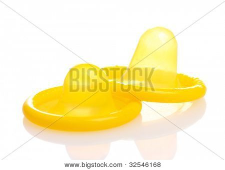 Two yellow condoms isolated on white