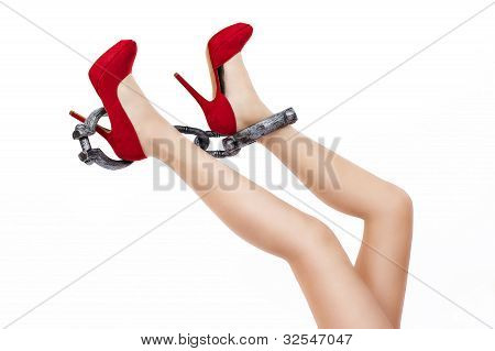 Slim Long Sexy Woman Legs In Stylish Red High Heels Shoes With Shackles On White Background