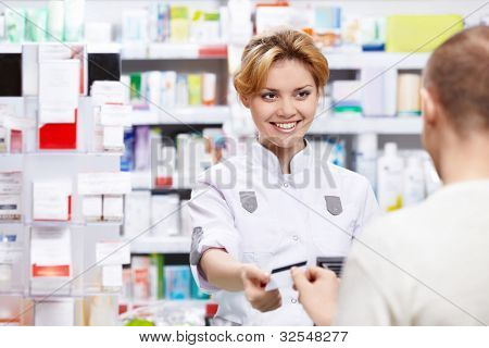 The pharmacist sells the medicine in a pharmacy