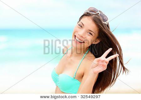 Happy beach vacation woman joyful smiling on beautiful tropical beach during summer holidays. Fresh mixed race Caucasian / Chinese Asian bikini model.