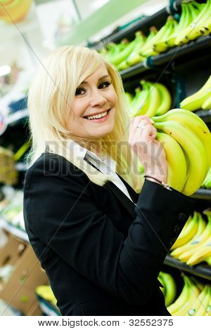 Attractive smiling blonde woman buying a bunch of bananas in a supermarket