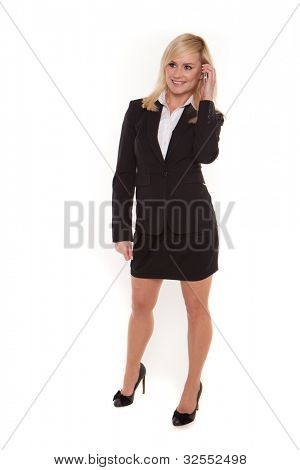 Blonde stylish businesswoman standing chatting on her mobile phone and looking off camera
