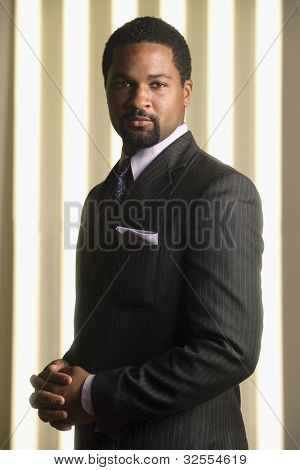 Portrait of African businessman with hands clasped