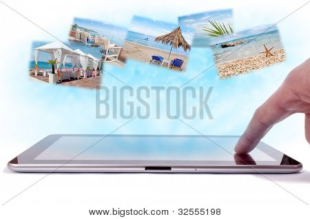 Finger on the tablet touch-screen and sea holiday images in the blue rays from tablet screen