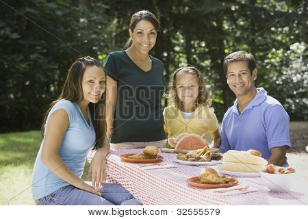 Portrait of Hispanic family at picnic table