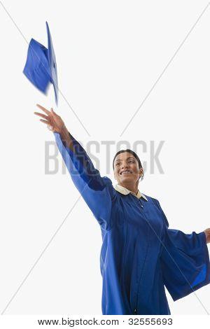 Studio shot of Indian woman throwing graduation cap in air
