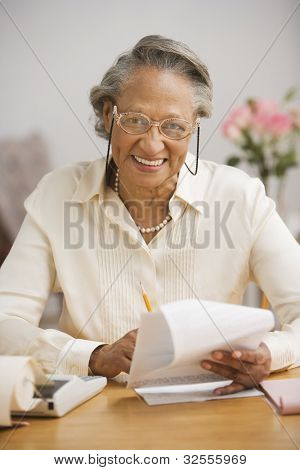 Senior African woman paying bills at table
