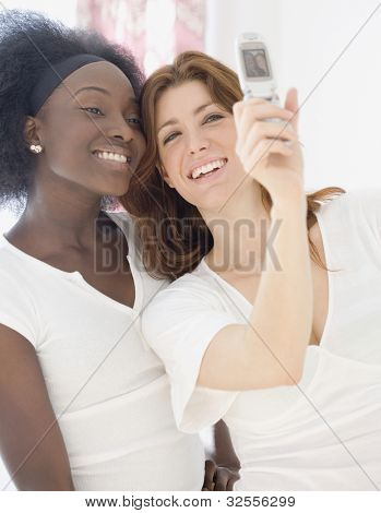 Two women taking photograph with cell phone