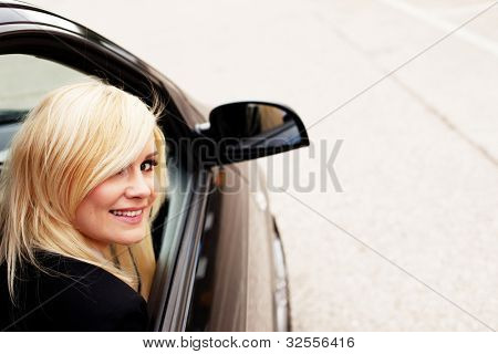 Pretty blonde gives a big smile from the passenger side of a modern automobile.