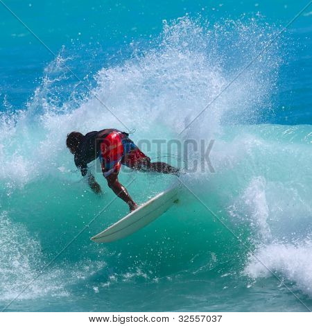 Young man surfing in tropical sea with blue water