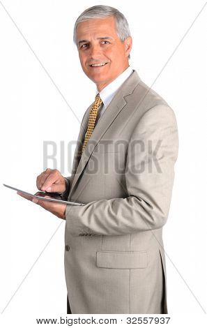 Portrait of a smiling middle aged businessman in a light suit with a tablet computer. Three quarters view over a white background.