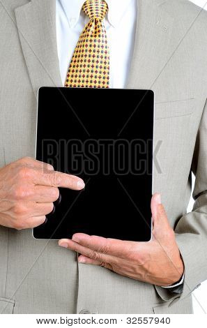 Closeup of a businessman in a suit pointing at the screen of a tablet computer. Man is unrecognizable, with tablet held in front of his torso.