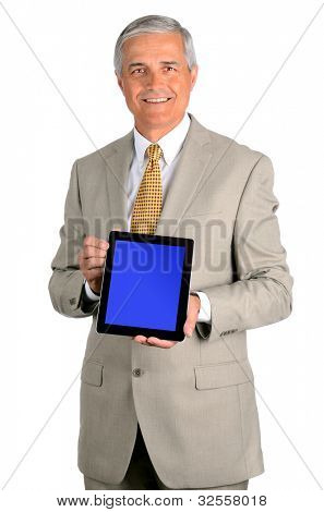 Portrait of a smiling middle aged businessman in a light suit with a tablet computer with display on blue screen. Three quarters view over a white background.