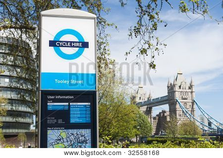 LONDON, UK - APRIL 30: A bicycle hire sign with Tower Bridge in the background. April 30, 2012 in London. The program, launched in 2010, aims to ease traffic in the  English capital.