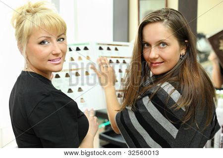 Happy client and hairdresser with catalog of hair colors look at camera in beauty salon
