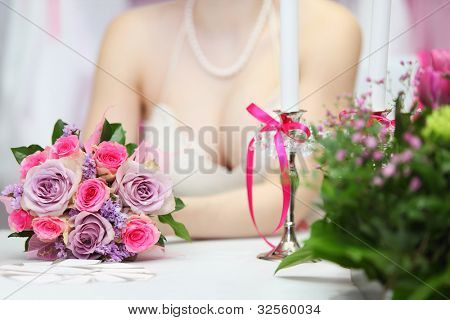 decollete of young bride wearing white dress, which sits at table with candles and holds bouquet of roses; focus on flowers