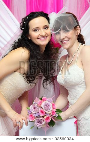 two happy brides wearing white dresses hold beautiful bouquet of roses; Focus on women on left