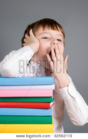 Boy With A Pile Of Books Yawns