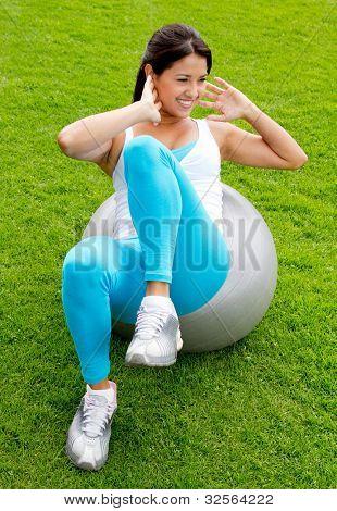 Mujer haciendo Pilates con pelota de un suizo - al aire libre