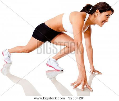 Female athlete in position to start running - isolated over a white background