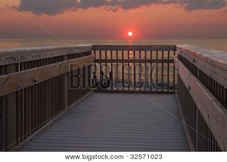 Sun Rising Over A Railing At The Beach