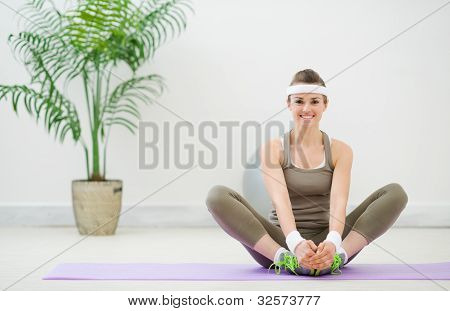 Smiling Woman In Sportswear Making Stretching Exercises