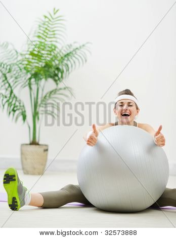Smiling Woman Sitting Behind Fitness Ball And Showing Thumbs Up
