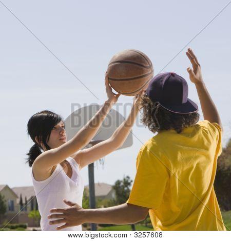 Two Teens Play Basketball