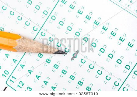 A number two pencil rests on a test form that is partially filled out.