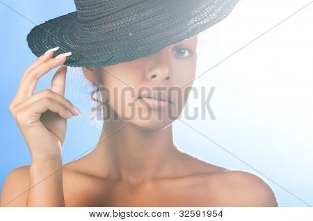 sunny beautiful mulatto woman wearing black straw hat on sky background