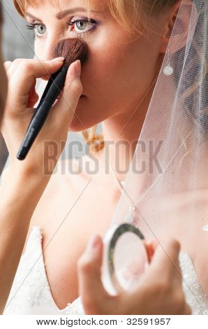 bride is doing make up for wedding celebration