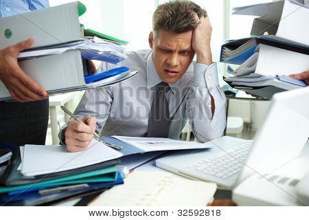 Contador perplejo haciendo informes financieros estar rodeados de socios con enormes pilas o