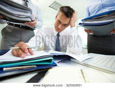 Perplexed accountant doing financial reports being surrounded by business partners with huge piles of documents
