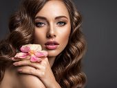 Stunning girl holds flower near eyes. Beautiful woman with brown hair. Woman with beauty long curly  poster