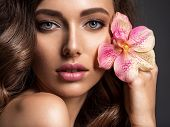Stunning girl holds flower near eyes. Beautiful woman with brown hair. Beauty treatments. Closeup po poster