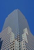 stock photo of modern building  - manhattan harbor side skyscraper financial district against a blue sky