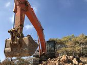 Excavator Scoop Loading A Soil During Road Construction. Load Angle View. Heavy Machinery At Earthmo poster