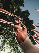 Smiling Bride Throws The Wedding Bouquet Of Her Friends poster
