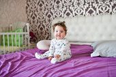 Portrait Of A Small Child Sitting On The Bed. Portrait Of A Little Baby Sitting On The Bed. Portrait poster