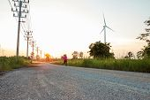 The Evening Sunset, The Area Of The Wind Turbine Generates Clean Energy Electricity, A Woman Is Jogg poster
