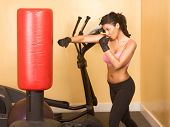 picture of spandex  - Attractive woman kickboxing using red punching bag - JPG