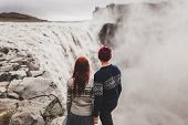 Young Couple In Love Looking At Famous Icelandic Landmark Dettifoss Waterfall. Traditional Wool Swea poster