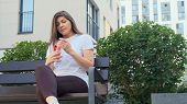A Young Woman Sits On A Bench In An Urban Environment, Drinks Water From A Plastic Bottle And Throws poster