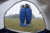 foto of sleeping bag  - Indian couple wrapped in sleeping bags at campsite - JPG