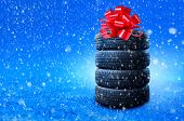 New Winter Tires Pile As A Gift. Tyres Pile With A Big Red Bow, As A Present Or Bonus For Buying A C poster