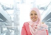 stock photo of muslimah  - Asian Muslim woman standing on modern office background - JPG