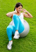 Woman doing Pilates with a Swiss ball -outdoors
