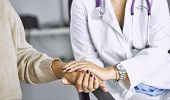 Woman Doctor Calms Patient And Holds Hand poster