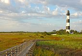stock photo of marsh grass  - Walkway leading to the Bodie Island lighthouse over marshes of the Cape Hatteras National Seashore against white clouds and a blue morning sky - JPG